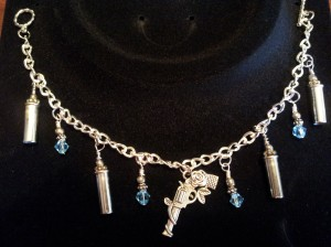 Bracelet with revolver charm, 22lr casing and blue crystals.