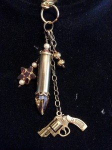 Bullet keychain with revolver charm, heart and brass beads.